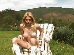Playful blonde shemale in boots masturbates outdoor