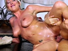 Oiled up blonde milf feasts on a rock hard meat pole
